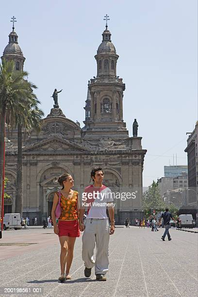 chile, santiago, young couple walking through square, holding hands - santiago chile fotografías e imágenes de stock