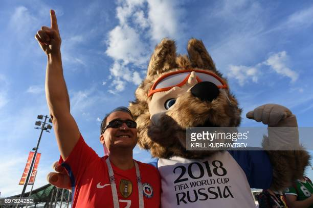 A Chile supporter poses with a person dressed as Zabivaka the mascot of the 2018 FIFA World Cup ahead of the 2017 Confederations Cup group B football...