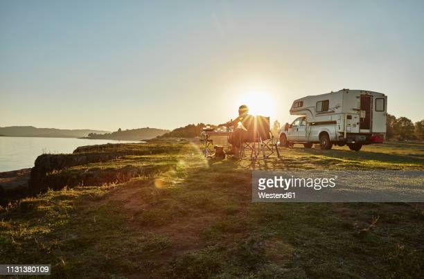 chile, talca, rio maule, camper at lake with woman and dog at sunset - convoy stock pictures, royalty-free photos & images