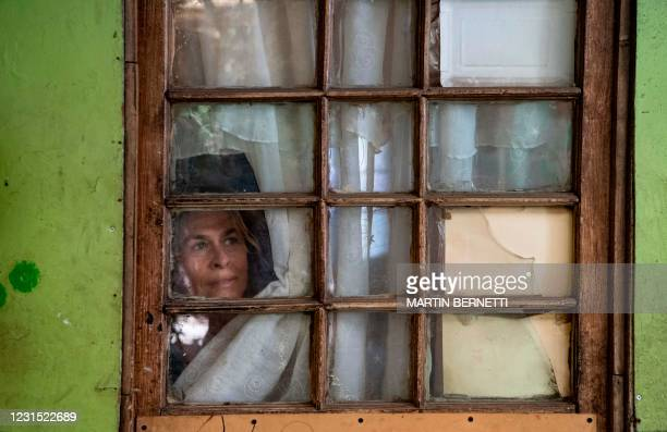 Chilean 60-year-old Pia Ortiz looks out of the window at her house in the Central Station commune of Santiago, on March 2, 2021. - Pia Ortiz lost her...