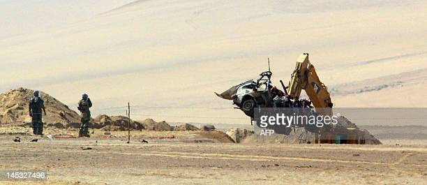 Chilean army personnel retrieve a civilian vehicle destroyed by an antitank mine near Los Escritos creek in Arica around 1600 km north of Santiago on...