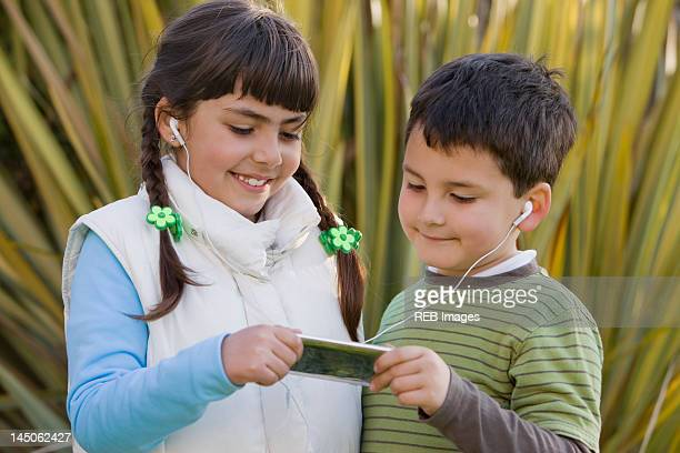 Chilean brother and sister sharing mp3 player