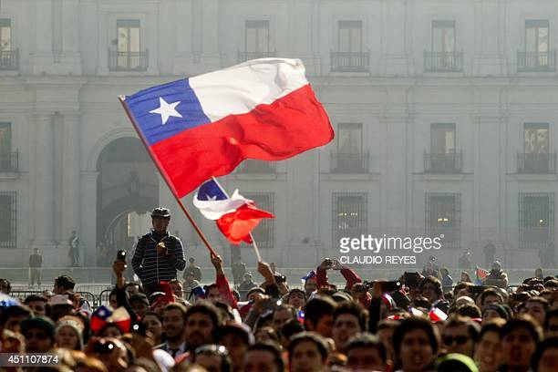 Chilean fans watch the live broadcast of the FIFA World Cup football match against the Netherlands on a giant screen at the Citizens' Square in front...