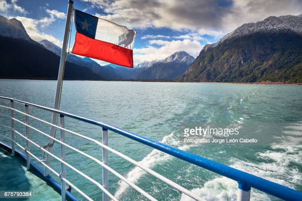 chilean flag against the mountains from the catamaran desk during the winter andean lake crossing - azul turquesa stock pictures, royalty-free photos & images