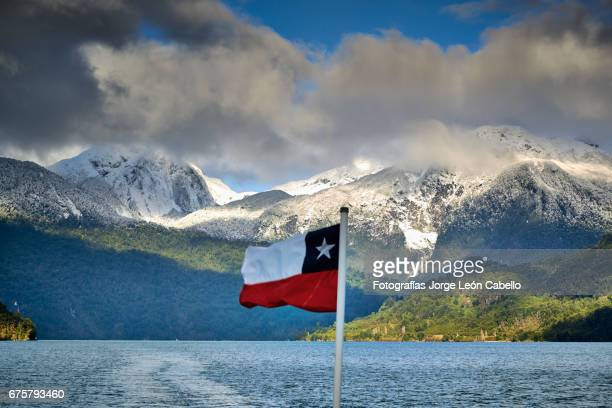 chilean flag against the mountains from the catamaran desk during the winterandean lake crossing - azul turquesa stock pictures, royalty-free photos & images