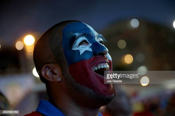 Chilean football team fan watches his team play against Australia on the giant screen showing the match at the FIFA World Cup Fan Fest on Copacabana...