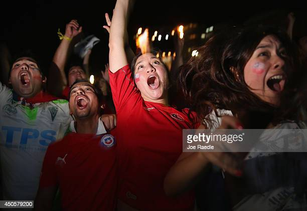 Chilean football team fans react as their team scores against Australia as they watch the game on the giant screen showing the match at the FIFA...
