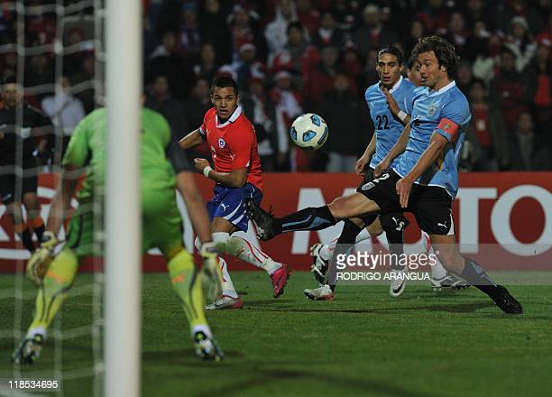 Chilean forward Alexis Sanchez eyes the ball as Uruguayan goalkeeper Fernando Muslera and defender Diego Lugano look on during the 2011 Copa America...