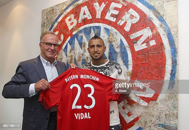 Chilean midfielder Arturo Vidal and Bayern Muenchen president Karl-Heinz Rummenigge hold Vidal's new jersey after he signed his contract with FC...