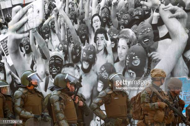 Chilean military stand in front of a mural as Antigovernment demonstrators protest against cost of living increases on October 20 2019 in Santiago...