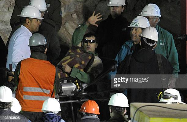 Chilean miner Raul Bustos waves as he is transported on a stretcher after being brought to the surface from the San Jose mine near Copiapo Chile on...
