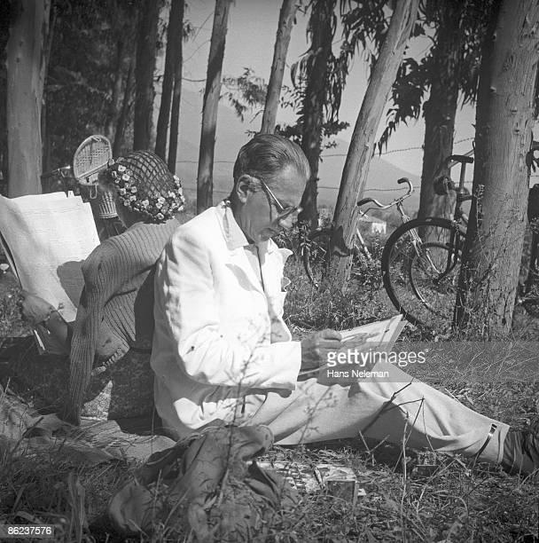 Chilean painter Laureano Guevara and wife Else sit back to back, he painting and she reading a newspaper, while they picnic on Echenique Avenue, La...