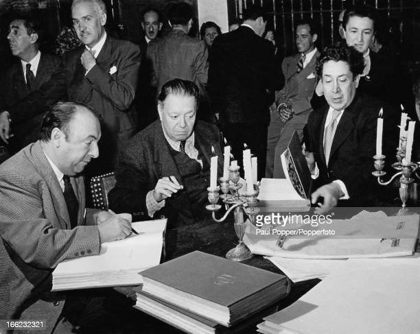 Chilean poet diplomat and politician Pablo Neruda and Mexican painters Diego Rivera and David Alfaro Siqueiros sign copies of Neruda's latest poetry...