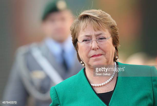 Chilean President Michelle Bachelet reviews a guard of honour with German Chancellor Angela Merkel upon Bachelet's arrival at the Chancellery on...