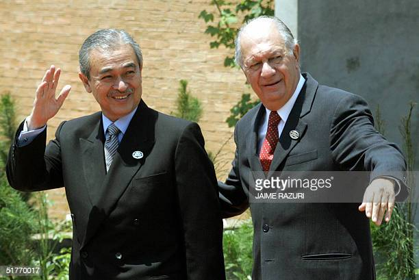 Chilean President Ricardo Lagos and Malaysian Prime Minister Abdullah bin Ahmad Badawi wave prior to the first session of the APEC Summit leaders, 20...