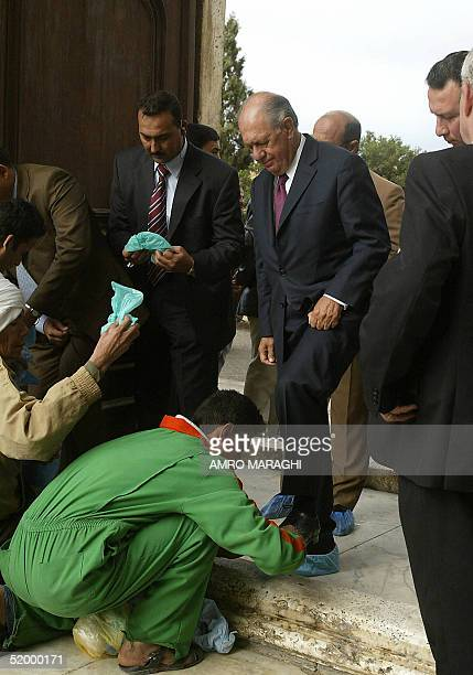 Chilean President Ricardo Lagos who is the first Chilean head of state to visit Egypt wears plastic bags as he enters the Salaheddin Citadel in Cairo...
