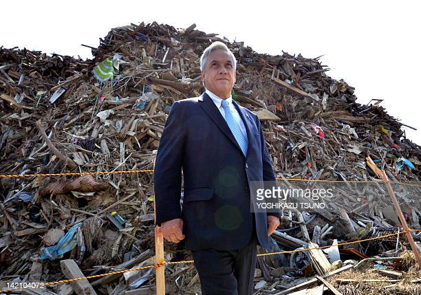 Chilean President Sebastian Pinera looks on as he stands in front of a pile of debris from the March 11 earthquake and tsunami in Minamisanriku town...