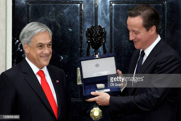 Chilean President Sebastian Pinera presents a rock from the San Jose mine to British Prime Minster David Cameron outside number 10 Downing Street on...