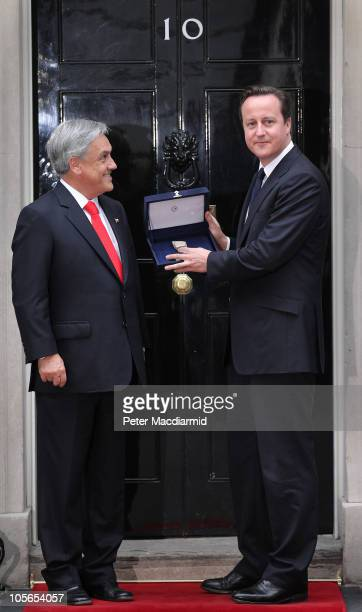 Chilean President Sebastian Pinera presents British Prime Minister David Cameron with a piece of rock from the San Jose mine at Downing Street on...