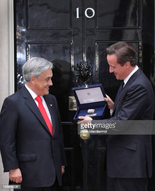 Chilean President Sebastian Pinera presents British Prime Minister David Cameron with a piece of rock from the San Jose mine in Downing Street on...