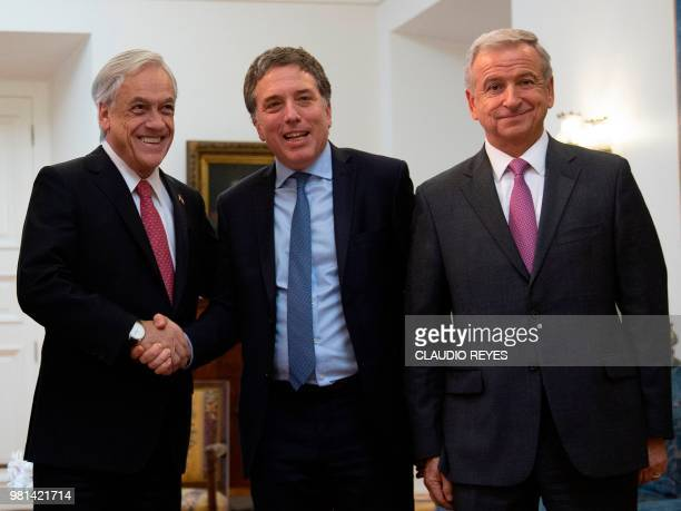 Chilean President Sebastian Pinera shakes hands with Argentina's Finance Minister Nicolas Dujovne next to Chilean Finance Minister Felipe Larrain...