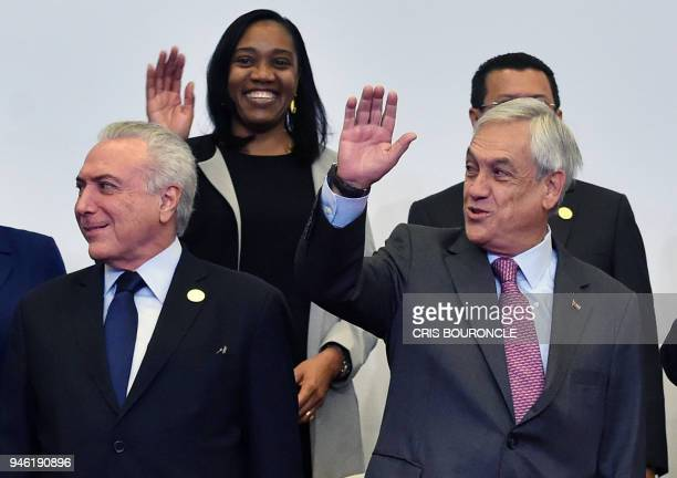 Chilean President Sebastian Pinera waves next to Brazilian President Michel Temer as they pose for the family photo of the Eighth Americas Summit in...