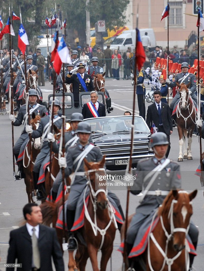 Chilean President Sebastian Pinera (L) waves to public as he arrives at the National Congress to give his annual message to the nation, in Valparaiso on May 21, 2010.