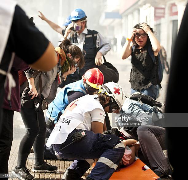 Chilean Red Cross volunteers assist a person overcome by tear gas during a students' demonstration demanding to the Chilean government better...