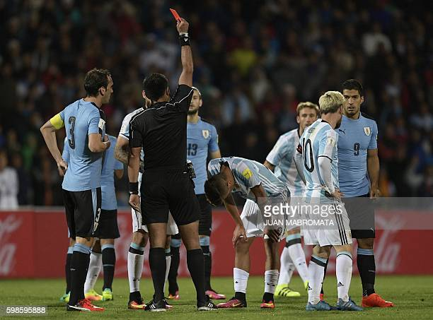 Chilean referee Julio Bascunan shows the red card to Argentina's Paulo Dybala during their Russia 2018 World Cup qualifier football match in Mendoza...