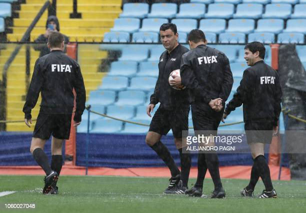 Chilean referee Roberto Tobar along with his team officials checks the water level in the pitch before suspending the Copa Libertadores 2018 final...