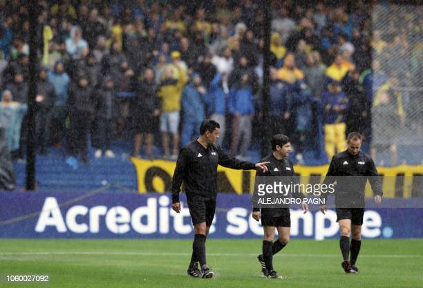 Chilean referee Roberto Tobar along with his team officials inspects the pitch before suspending the Copa Libertadores 2018 first leg final football...