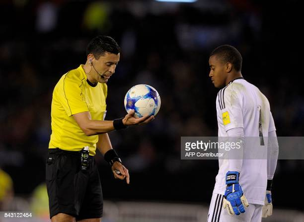Chilean referee Roberto Tobar and Venezuela's goalkeeper Wuilker Farinez during the 2018 World Cup qualifier football match between Argentina and...
