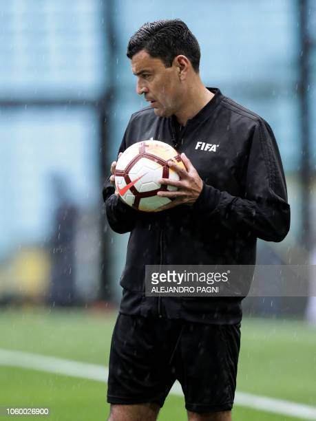 Chilean Referee Roberto Tobar checks the water level in the pitch before suspending the Copa Libertadores 2018 final first leg football match between...