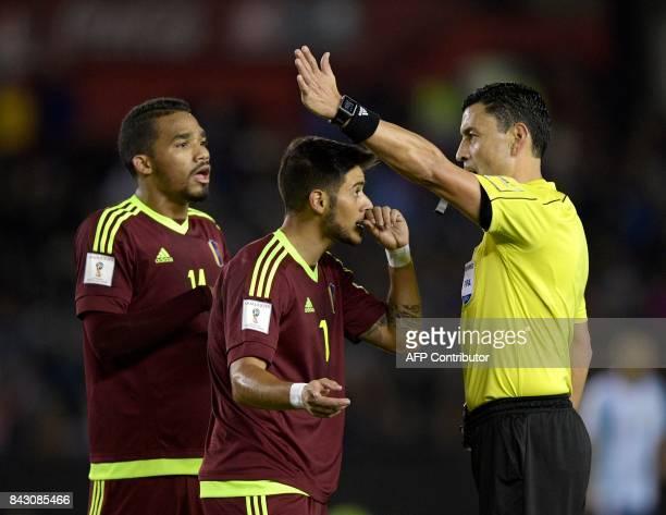 Chilean referee Roberto Tobar speaks with Venezuela's Darwin Machis and Yangel Herrera during the 2018 World Cup qualifier football match between...