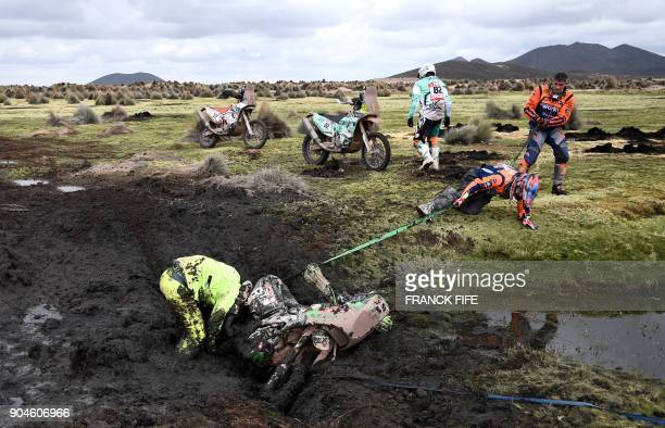 Chilean rider Patricio Cabrera is helped by other competitors as he digs his bike out of the mud during Stage 7 of the 2018 Dakar Rally between La...