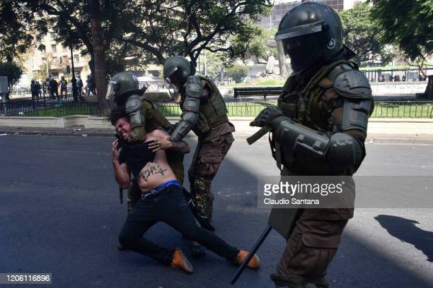 Chilean riot police arrest a demonstrator during protests as part of the International Women's Day on March 8 2020 in Santiago Chile