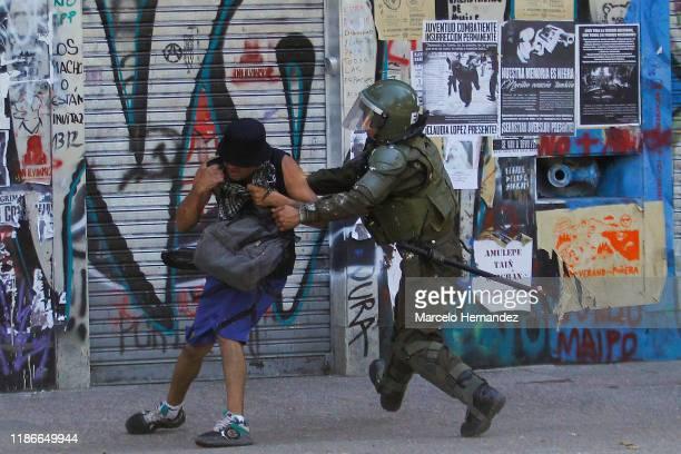 Chilean riot police officer arresta a demonstrator during protests against president Sebastian Piñera at Plaza Italia on December 5, 2019 in...