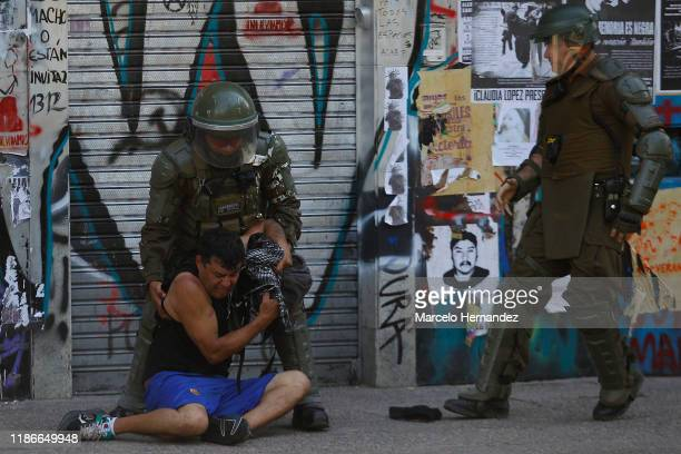 Chilean riot police officers arrest a demonstrator during protests against president Sebastian Piñera at Plaza Italia on December 5 2019 in Santiago...