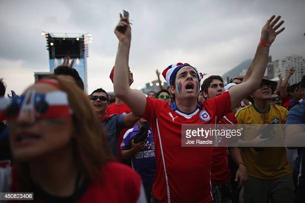 Chilean soccer team fans watch as their team plays against Spain while watching it on the screen setup at the FIFA Fan Fest during the World Cup...
