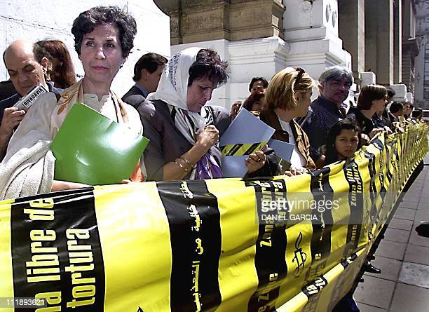 Chilean socialist deputy Isabel Allende unfurls a long banner with legend in different languages to end the use of torture with the members of Human...