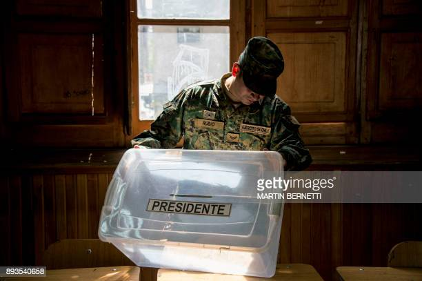 Chilean soldier checks a ballot box at a polling station at the Amunategui highschool in Santiago on December 15 2017 during preparations ahead of...