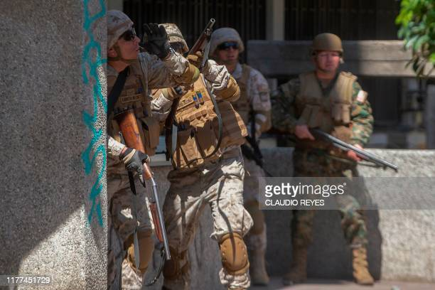 Chilean soldier shoots against demonstrators in Santiago Chile on October 21 2019 Violent protests initially against a hike in metro fares first...