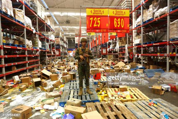 A chilean soldier stands guard at a supermarket after it was ransacked on October 22 2019 in Santiago Chile After President Sebastian Piñera...