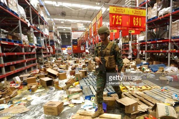 Chilean soldier stands guard at a supermarket after it was ransacked on October 22, 2019 in Santiago, Chile. After President Sebastian Piñera...