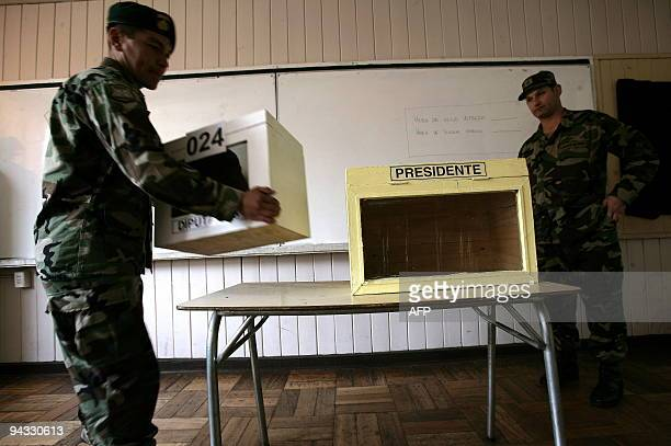 Chilean soldiers carry polling boxes in a public school in Valdivia some 800 km south of Santiago on December 12 2009 which will be used as a voting...