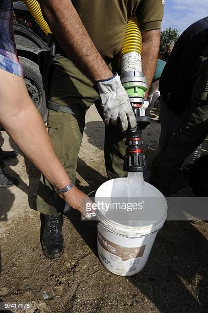 Chilean soldiers distribute potable water in the football stadium in Constitucion Chile on March 3 2010The official death toll from Saturday's...