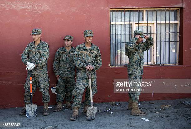 Chilean soldiers take a break as they work on September 17 2015 on the cleaning of Tongoy sea ressort 400 kilometres north of Santiago hit on the eve...