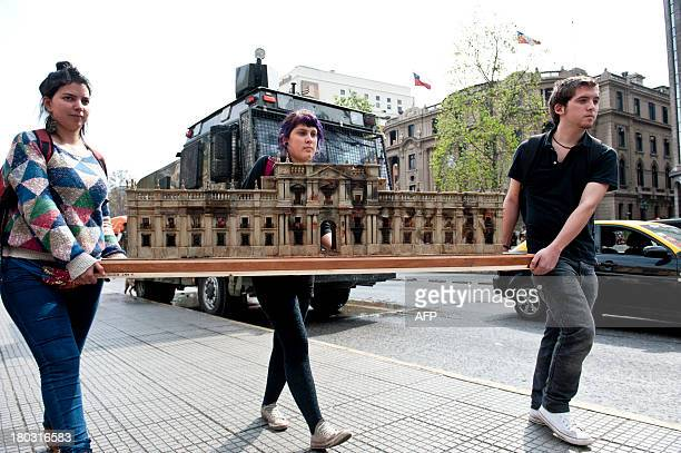 Chilean students carry a scale model of the presidential palace as it looked after the airstrike carried out by the rebellious forces of General...