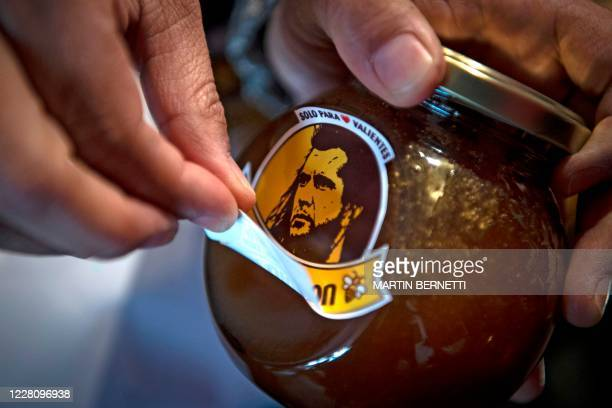 Chilean unemployed teacher Yohana Agurto, removes the label from a jar of 'Miel Gibson' organic honey, at her home in Santiago, on August 18, 2020. -...