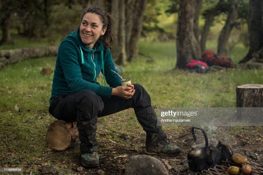 Chilean woman drinks yerba mate tea while camping : Stock-Foto